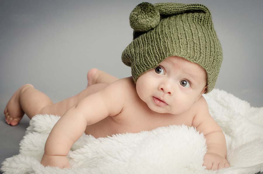 New born Baby with sparkle eyes wearing green hat