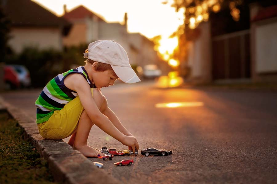 Cute little boy, playing with little toy cars on the street on sunset, summertime